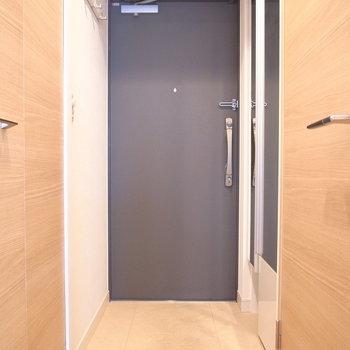 やさしい色合いの中、玄関ドアの黒色がアクセントに。