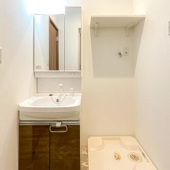左手には鏡の大きな洗面台。洗濯機置場の上には便利な棚も付いています。