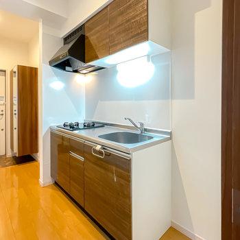 ドアを抜けて右手に木目調のキッチン。冷蔵庫置き場もすぐ横に。