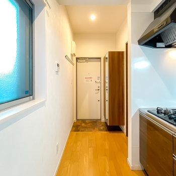 玄関はキッチンの奥に。ここにも窓があって、料理の匂いもこもりにくいんです。