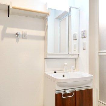 右側には木目調の洗面台。シャンプードレッサー仕様で鏡の裏は収納に。