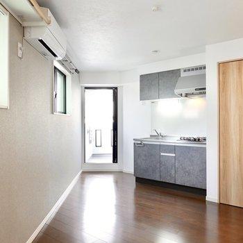 玄関から階段を上がった先に居室。正面にはキッチンとクローゼット、ベランダへのドアが。