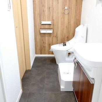 トイレ側の木目調の壁とタイル風の黒い床の組み合わせがカッコいい……!