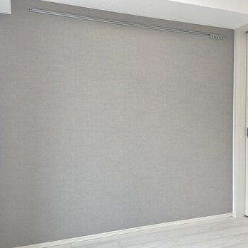 ライトグレーのアクセントクロスにはピクチャーレールもついています。※写真は3階の反転間取り別部屋のものです