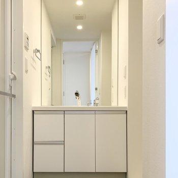 左側のドアの中がサニタリー。大きなミラーが素敵。(※写真は8階の同間取り別部屋のものです)