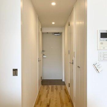 キッチンの後ろのドアの向こうに水廻りが。(※写真は8階の同間取り別部屋のものです)