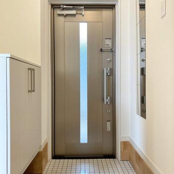 白のタイルで汚れも落としやすい玄関。