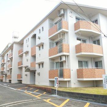 3階建ての横に長い建物。敷地内にに駐車場もあります。