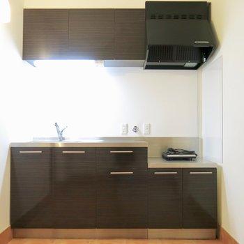 キッチンはダークブラウンでシックな雰囲気に※写真は同間取り別部屋のもの