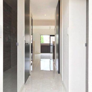 玄関を開けたところから始まる白い床。ダウンライトに照らされツヤツヤ輝きます。