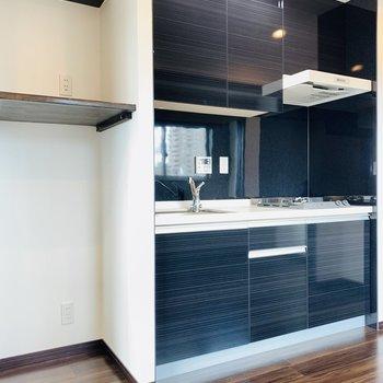 お洒落な黒のキッチン。お隣には冷蔵庫のおスペース。