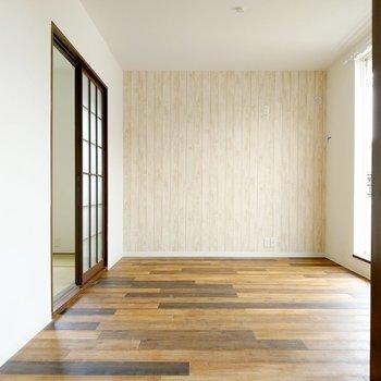 深い木目の床に淡いカラーのアクセントクロス。家具は白で揃えたい。