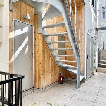 玄関前共用部。オレンジな木材とグレーのコントラストが素敵。