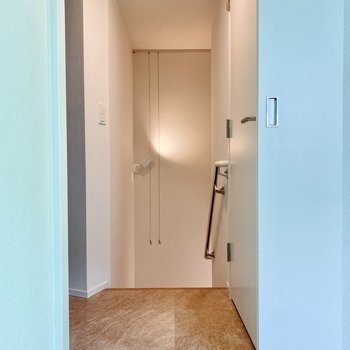 【洋室】サニタリーへ。階段にもピクチャーレールがありますね。