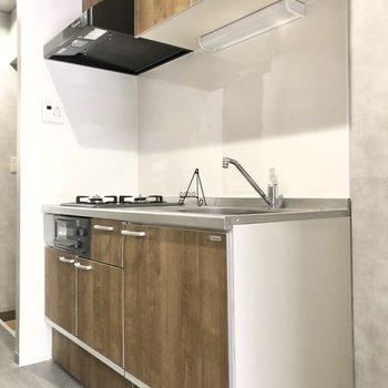 キッチンも木目のクールなデザイン。右横には冷蔵庫を置くスペースもあります。