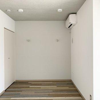 シンプルな壁と天井に様々な色を組み合わせた床が映えますね。奥のさりげないアクセントクロスもポイント。