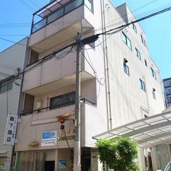 下町の雰囲気がある住宅地のマンション。1階にはお店が入っています。