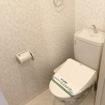 おトイレは玄関脇に。上部には棚もあります。