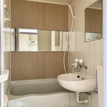 ワイドな鏡と、木目調の壁材がオシャレ。