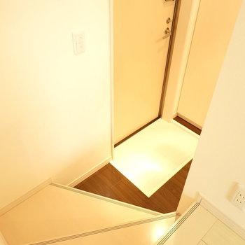 リビングから1段下がったところに玄関。(※写真は1階の反転間取り別部屋のものです)