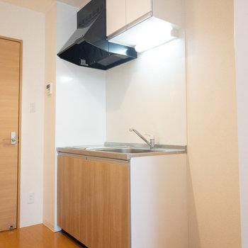 扉や床の色と調和したキッチン。