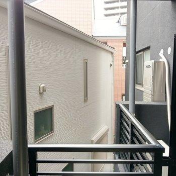 正面は建物裏手。201号室のバルコニーが見えます。