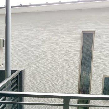 正面は建物裏手。202号室のバルコニーがちらっと見えます。