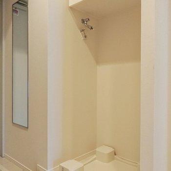 玄関横に洗濯機置き場。棚付きです。※写真は9階の同間取り別部屋のものです