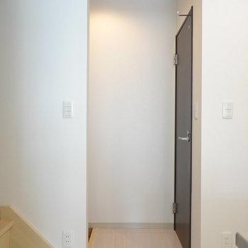 キッチン後ろには玄関。右側のドアを開けるとトイレ。(※写真は同間取り別部屋のものです)