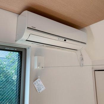 エアコン下からキッチン横まで、収納式ワイヤーの物干しがあります。