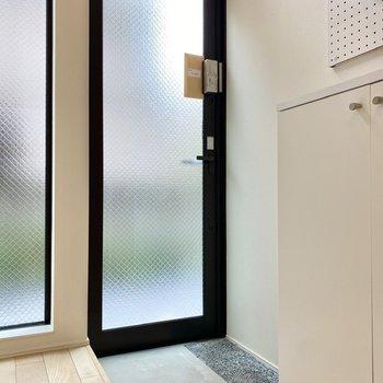 玄関はスモークガラスで光を取り入れます。カーテンで目隠しすることもできますよ。