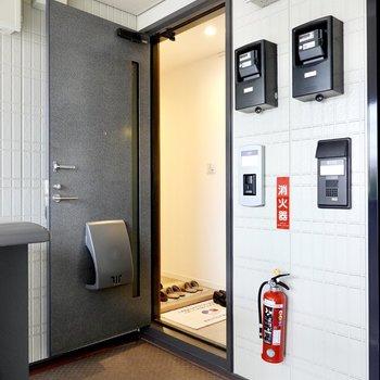 玄関前の共用部はモノトーンのスッキリとした空間。