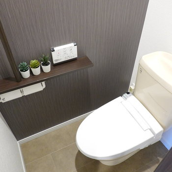 トイレはシックで落ち着きのある空間。ウォシュレット付きで、頭上には収納もあります。