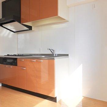 オレンジの明るいキッチンの横には冷蔵庫などを置ける広めのスペース。(※写真は9階の同間取り別部屋のものです)