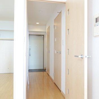 四角いガラスの嵌ったドアを開けて廊下へ。手前が脱衣所、奥がトイレのドア。(※写真は9階の同間取り別部屋のものです)