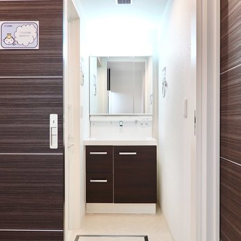 脱衣所は対面側に。スペースたっぷりで、大きな鏡の洗面台も。(※写真は6階の同間取り別部屋のものです)