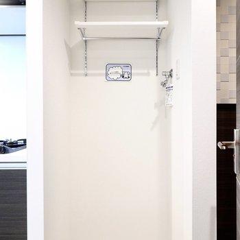 洗濯置き場はキッチン右側に。便利な棚が備え付き。(※写真は6階の同間取り別部屋のものです)