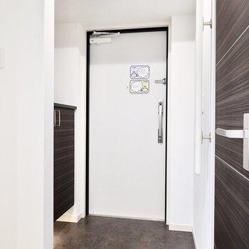 玄関は黒いタタキがクール。靴箱は左手に。(※写真は6階の同間取り別部屋のものです)