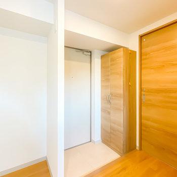 玄関は家電スペースのすぐ隣に。靴箱も木目調で揃えられています。