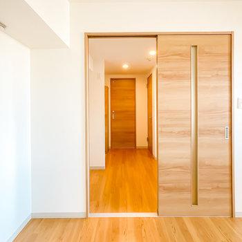 木目調の引き戸の先はキッチンスペース。奥には脱衣所やトイレも。