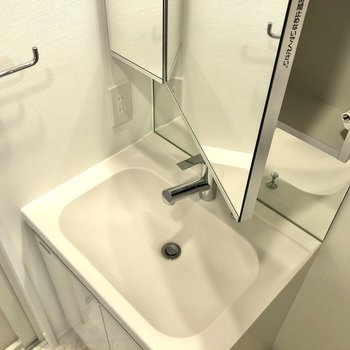 洗面台にはタオルかけやコンセントが。鏡の内側は収納になっています。※写真は12階の反転間取り別部屋のものです