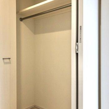 収納です。コートなどがかけられるパイプも渡っています。※写真は12階の反転間取り別部屋のものです