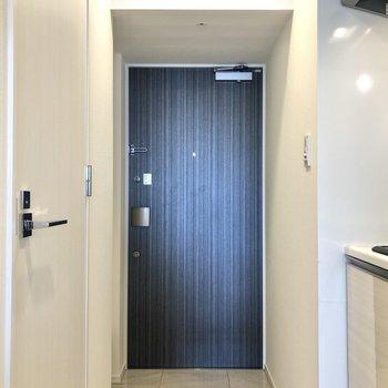 白い大理石調の床材が使われている玄関。※写真は12階の反転間取り別部屋のものです