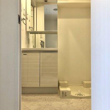 振り返ると、洗濯機置き場、洗面台、浴室があります。※写真は12階の反転間取り別部屋のものです