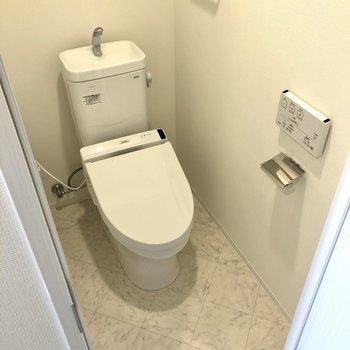 洗面室の隣にはトイレが。※写真は12階の反転間取り別部屋のものです