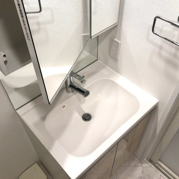 鏡の内側が収納になってる洗面台にはタオル掛けやコンセントも。