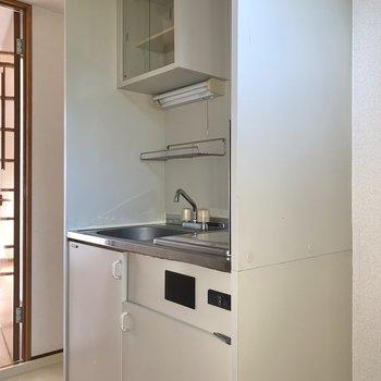 キッチンはコンパクトながら上部に収納が付いていますよ。※写真は通電前・フラッシュを使用しています