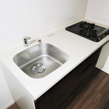キッチンは2口コンロのシステムキッチンです。(※写真は10階の同間取り別部屋のものです)
