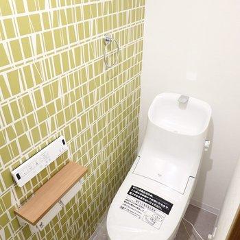 鮮やかなグリーンの壁の横には、ウォシュレット付きのトイレ。スタイリッシュなフォルムで見ているだけでも楽しい!