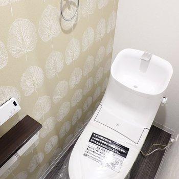 植物のような模様のクロスの横には、ウォシュレット付きのトイレ。スタイリッシュなフォルムで見ているだけでも楽しい!